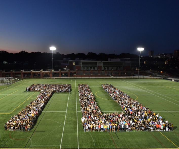 Students form a T and U on Towson's football field